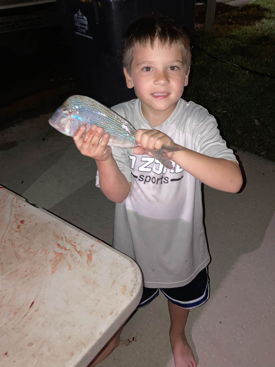 Child showing his catch from a Fish Huge Charter